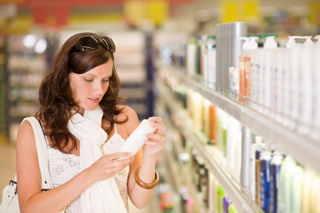 Frau vor Shampoo-Regal